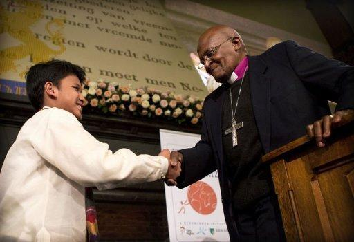 "Desmond Tutu (R) shakes hands with Cris ""Kesz"" Valdez after awarding him with the Children's Peace Prize"