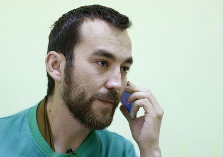 A man, according to Ukraine's state security service (SBU) is named Yevgeny Yerofeyev and is one of two Russian servicemen recently detained by Ukrainian forces, tries to call his relatives on a mobile phone at a hospital in Kiev, Ukraine, May 28, 2015. REUTERS/Valentyn Ogirenko