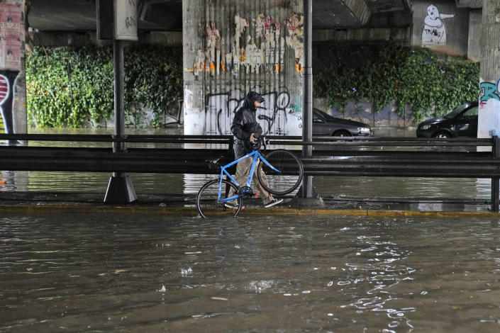 A man carries his bicycle as walks under a flooded underpass, in Athens, Thursday, Oct. 14, 2021. Storms battered the Greek capital and other parts of southern Greece, causing traffic disruption and some road closures. (AP Photo/Thanassis Stavrakis)