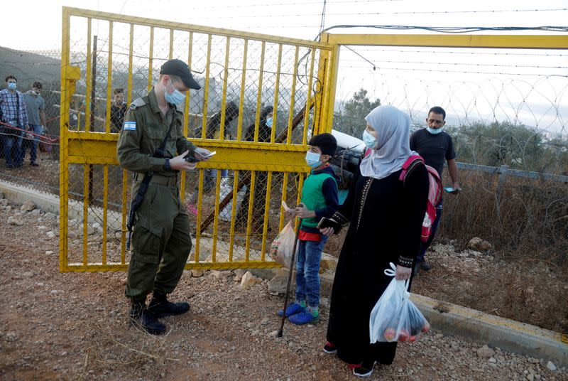 An Israeli soldier checks the documents of Palestinians crossing through the gate of a fence, part of the Israeli barrier, as they make their way towards an olive field, in Salfit in the Israeli-occupied West Bank