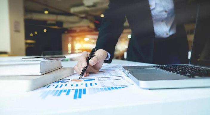 A photo of a businesswoman pointing at charts on a piece of paper on a table.