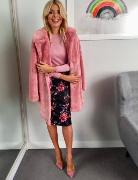 """<p>Amazingly, Holly's faux fur pink coat is still in stock on <a rel=""""nofollow noopener"""" href=""""http://www.very.co.uk/v-by-very-fauxnbspfur-coat-pink/1600176605.prd"""" target=""""_blank"""" data-ylk=""""slk:Very"""" class=""""link rapid-noclick-resp"""">Very</a>. Unfortunately, her River Island skirt is no longer in stock but we managed to find a pretty similar <a rel=""""nofollow noopener"""" href=""""https://www.riverisland.com/p/blue-floral-print-satin-finish-pencil-skirt-710391"""" target=""""_blank"""" data-ylk=""""slk:alternative"""" class=""""link rapid-noclick-resp"""">alternative</a> if you're interested… </p>"""