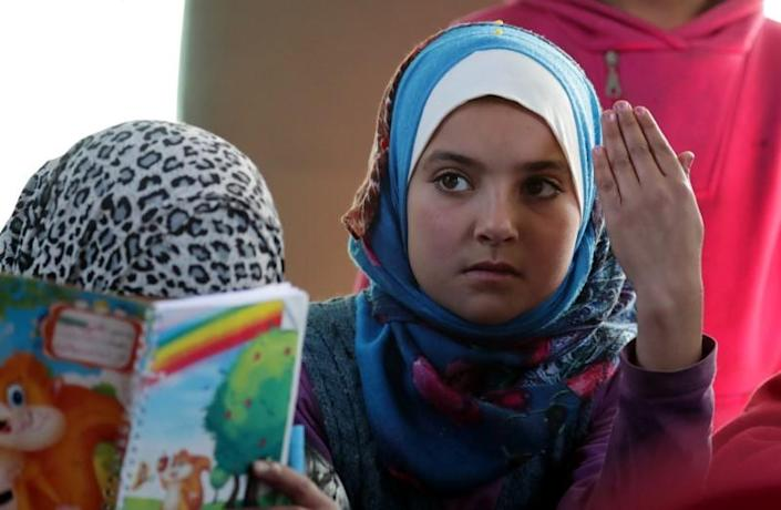 A student gestures as she attends a class inside a bus in the city of al-Bab