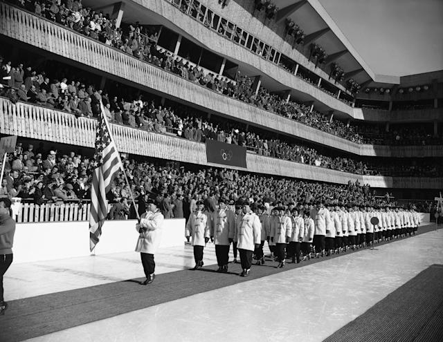 Jim Bickford, 43-year-old bobsledder from Saranac Lake, N.Y., carries U.S. flag as he leads teammates past stands at stadium at Cortina D?Ampezzo during opening ceremonies for 1956 Winter Olympic Games, Jan. 26, 1956, Cortina D?Ampezzo, Italy. Bickford, a forest ranger, is participating in his fourth Olympics. (AP Photo)