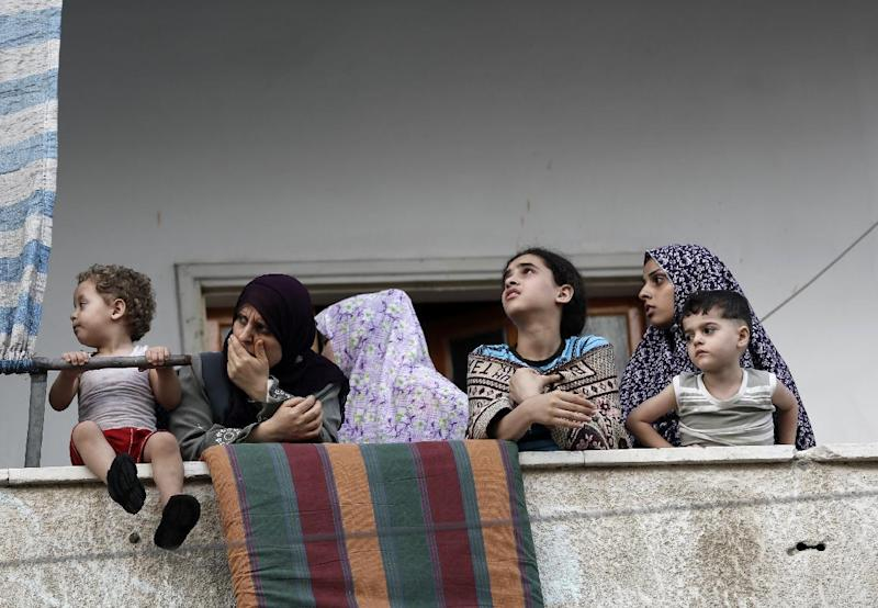 A Palestinian family stand at the balcony of their house as they look at a neighboring building which was targeted in an Israeli military strike in Gaza City on July 12, 2014 (AFP Photo/Mohammed Abed)