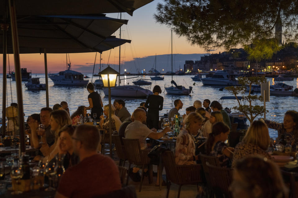 Holidaymakers sit in a seafront restaurant, in the Adriatic town of Rovinj, Croatia, Friday, Aug. 27, 2021. Summer tourism has exceeded even the most optimistic expectations in Croatia this year. Beaches along the country's Adriatic Sea coastline are swarming with people. Guided tours are fully booked, restaurants are packed and sailboats were chartered well in advance. (AP Photo/Darko Bandic)