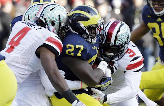 Michigan running back Derrick Green (27) is stopped by Ohio State safety C.J. Barnett (4) and defensive back Corey Brown (3) during the first quarter of an NCAA college football game in Ann Arbor, Mich., Saturday, Nov. 30, 2013. (AP Photo/Carlos Osorio)