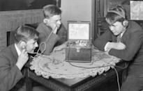<p>A group of young boys gather around the table to listen to the radio. The 1920s saw a huge boom in consumer radios, which were still a relatively new invention.</p>