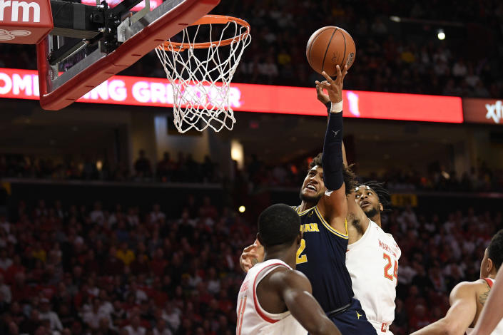 Michigan forward Isaiah Livers (2) goes to the basket between Maryland forward Donta Scott (24) and guard Darryl Morsell (11) during the first half of an NCAA college basketball game, Sunday, March 8, 2020, in College Park, Md. (AP Photo/Nick Wass)