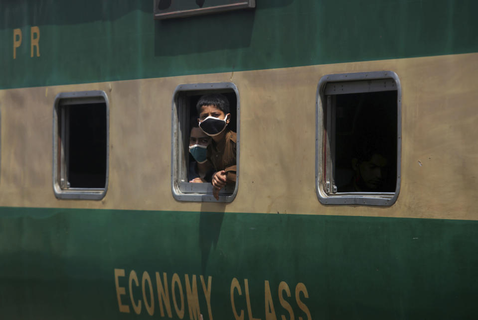 Boys wearing protective masks to help curb the spread of the coronavirus, look out the window of a train at a railway station, in Karachi, Pakistan, Saturday, Jan. 6, 2020. (AP Photo/Fareed Khan)