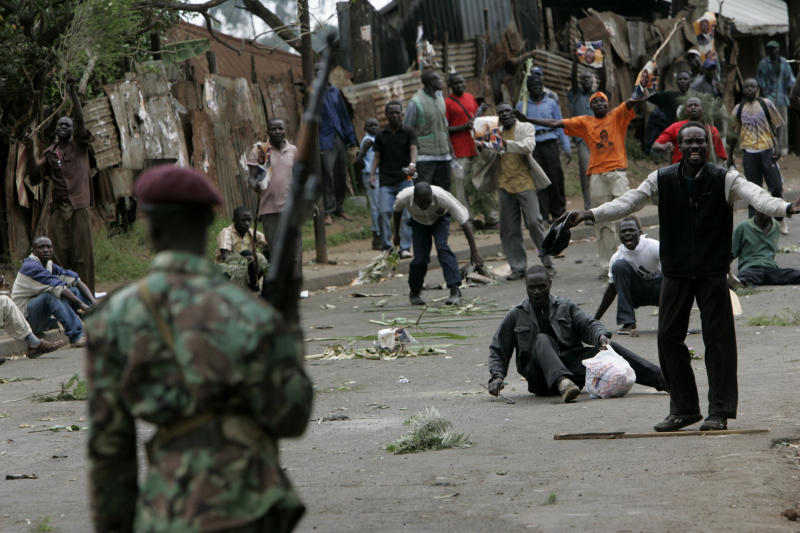 FILE - In this Monday, Dec. 31, 2007 file photo, opposition supporters taunt armed police during post-election riots in the Kibera slum of Nairobi, Kenya. One of Kenya's most vilified institutions - its police force - will be in the spotlight next week after the country's election on Monday, March 4, 2013 as it tries to prevent the same type of post-election bloodbath that Kenya suffered during its last presidential election. (AP Photo/Karel Prinsloo, File)