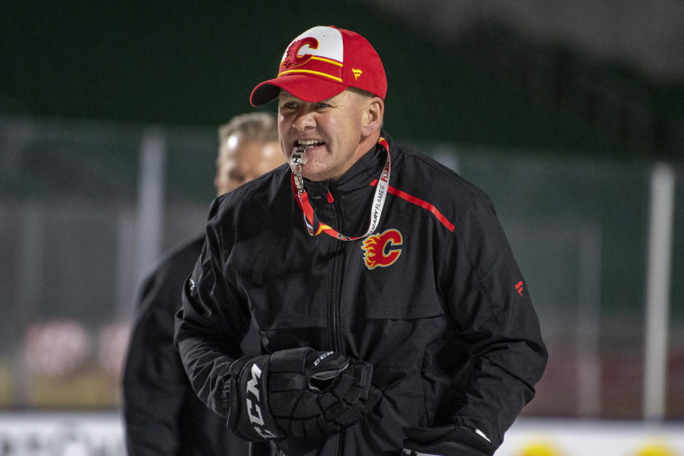 FILE - In this Oct. 25, 2019, file photo, Calgary Flames coach Bill Peters watches practice in Regina, Saskatchewan, ahead of the NHL Heritage Classic outdoor hockey game against the Winnipeg Jets. Calgary Flames general manager Brad Treliving said the team is looking into an accusation that head coach Bill Peters directed racial slurs toward a Nigerian-born hockey player a decade ago in the minor leagues, then arranged for the players demotion when he complained. Akim Aliu tweeted Monday, Nov. 25, 2019, that Peters dropped the N bomb several times towards me in the dressing room in my rookie year because he didnt like my choice of music. (Liam Richards/The Canadian Press via AP, File)