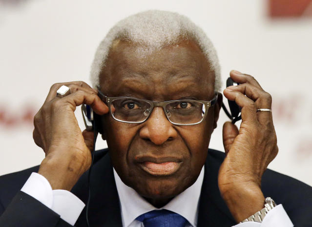 FILE - In this Aug. 21, 2015, file photo, then-IAAF president Lamine Diack adjusts his headphones during a joint IOC and IAAF news conference on the site of the World Athletic Championships in Beijing. One of the biggest sports corruption cases to reach court is being heard in Paris. The trial will hear allegations that Russian athletes paid millions of dollars to cover up their suspected doping in order to compete at the Olympic Games in 2012 and other competitions. Accused recipients of the payments include Lamine Diack, who presided for nearly 16 years at track and fields governing body. (AP Photo/Kin Cheung, File)