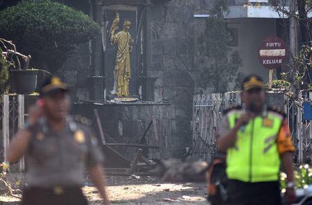 Police are seen outside the Immaculate Santa Maria Catholic Church following a blast, in Surabaya, East Java