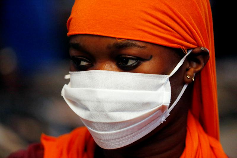 A woman wears a white face mask and covers her hair with an orange fabric.