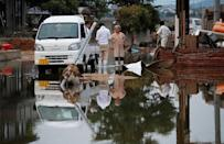Local residents stand in a flooded area in Mabi town in Kurashiki, Okayama Prefecture, Japan, July 12, 2018. REUTERS/Issei Kato