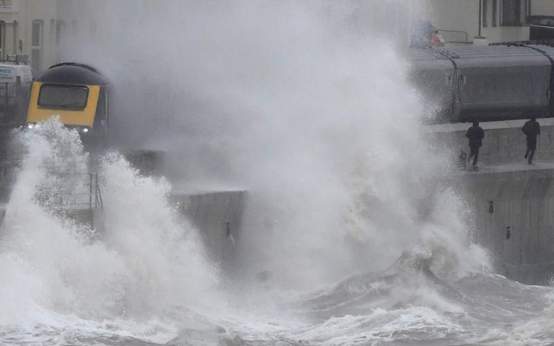 Large waves hit the sea wall as a train passes through Dawlish, in Devon, on Tuesday as Storm Brendan brings high winds and heavy rain - REUTERS