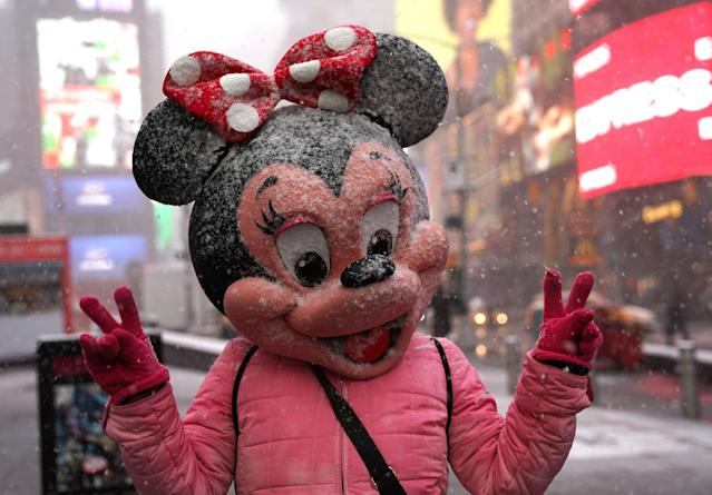 <p>A person in a Minnie Mouse mask poses Times Square in New York on March 21, 2018, as the fourth nor'easter in a month hits the tri-state area on the first full day of spring. (Photo: Timothy A. Clary/AFP/Getty Images) </p>