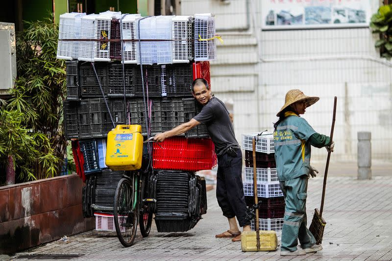 A man moves a bicycle loaded with plastic boxes as he passes woman cleaning the street in Guangzhou