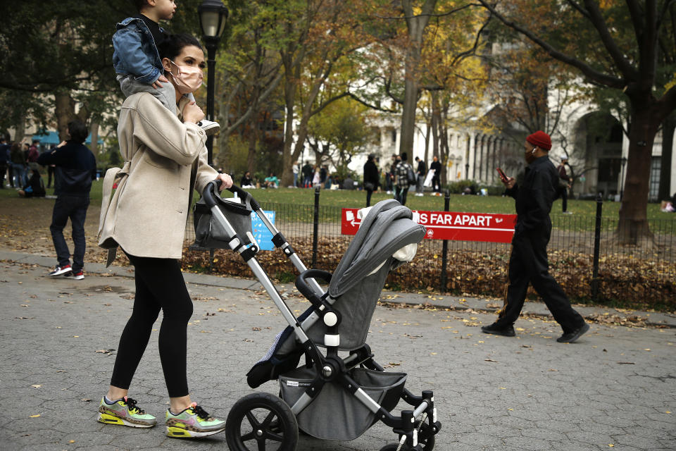 NEW YORK, NEW YORK - NOVEMBER 21: A woman wearing a protective mask pushes a stroller with her child on her shoulders on November 21, 2020 in New York City. The pandemic has caused long-term repercussions throughout the tourism and entertainment industries, including short-term and permanent closures of historic and iconic venues, and costing the city and businesses billions in revenue. (Photo by John Lamparski/Getty Images)