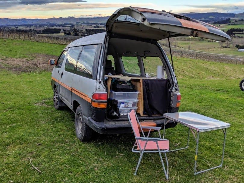 A van in a field with the trunk open and a table and chair in the grass