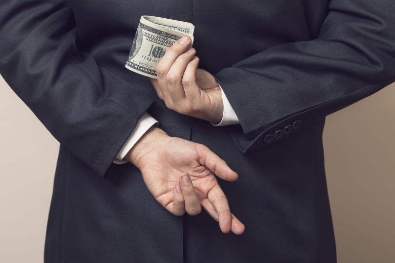 A businessman crosses his fingers behind his back while holding a wad of hundred dollar bills.