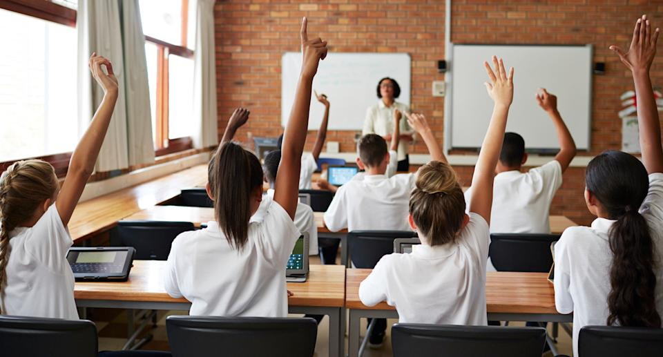 Pictured is a group of students in a classroom holding their hands up in front of a teacher.