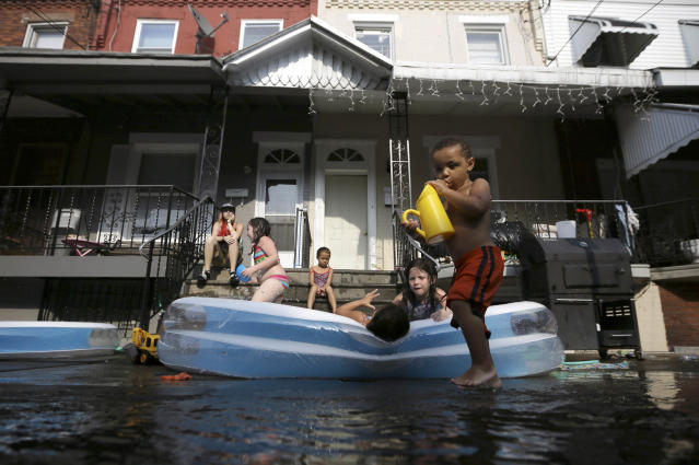 Jayden Jones, from right, 2, Veronica Caines, 6, Aliyah Nguyen, 5, Kianna Roman, 4, and Juliann Esola, 5, cool off in a wade pool under the watch of Amber Escola, Monday, July 16, 2012, in Philadelphia. Temperatures in Philadelphia reached the low 90s on Monday. (AP Photo/Matt Slocum)