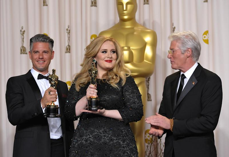 """Adele and Paul Epworth pose with their award for best original song for """"Skyfall"""" with presenter Richard Gere during the Oscars at the Dolby Theatre on Sunday Feb. 24, 2013, in Los Angeles. (Photo by John Shearer/Invision/AP)"""