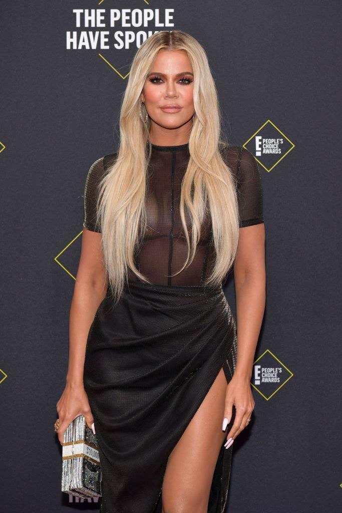 Khloe posing at the E People's Choice Awards in a dress with a see-through top and carrying a clutch in the shape of a stack of cash