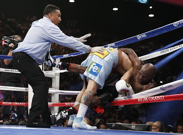 Marcos Maidana, center, from Argentina, knocks Floyd Mayweather Jr. through the ropes in their WBC-WBA welterweight title boxing fight Saturday, May 3, 2014, in Las Vegas. At left is referee Tony Weeks. (AP Photo/Eric Jamison)