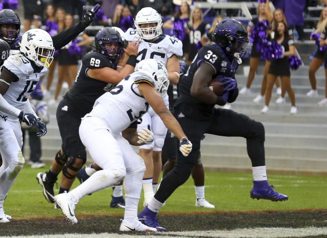 TCU running back Sewo Olonilua (33) scores a touchdown against West Virginia in an NCAA college football game Friday, Nov. 29, 2019, in Fort Worth, Texas. (AP Photo/Richard W. Rodriguez)