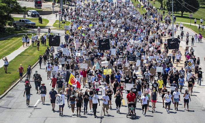 Marchers walk along a street during a rally to remember James Scurlock on Sunday, 7 June 2020, in Omaha.