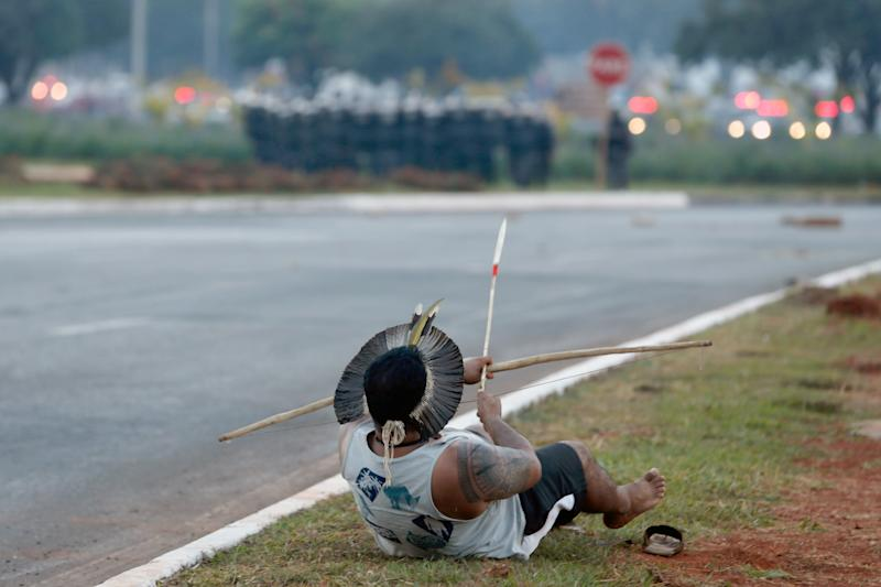 An Indigenous protester in traditional headdress gets ready to fire an arrow against the military police