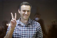 Russian opposition leader Alexei Navalny gestures as he stands in a cage in the Babuskinsky District Court in Moscow, Russia, Saturday, Feb. 20, 2021. Two trials against Navalny will be held: Moscow City Court will consider an appeal against his imprisonment in the embezzlement case and Babushkinsky District Court will announce a verdict in the defamation case. (AP Photo/Alexander Zemlianichenko)