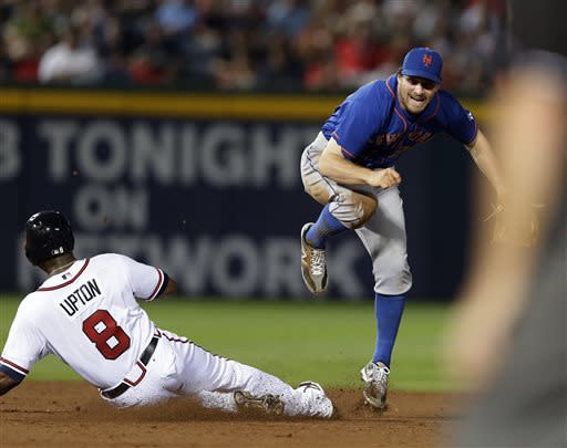 New York Mets second baseman Daniel Murphy, back right, avoids Atlanta Braves' Justin Upton (8) while turning a a double play on a B.J. Upton ground ball in the seventh inning of a baseball game on Thursday, June 20, 2013, in Atlanta. (AP Photo/John Bazemore)