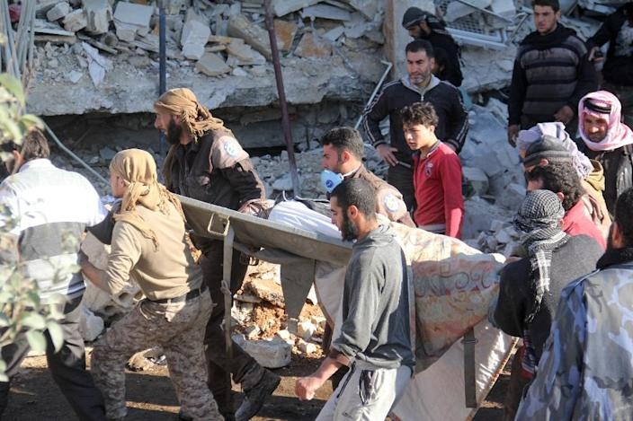 People carry a stretcher amid the debris after a hospital was hit by air strikes near Maaret al-Numan, in Syria's northern province of Idlib, on February 15, 2016 (AFP Photo/Omar haj kadour)
