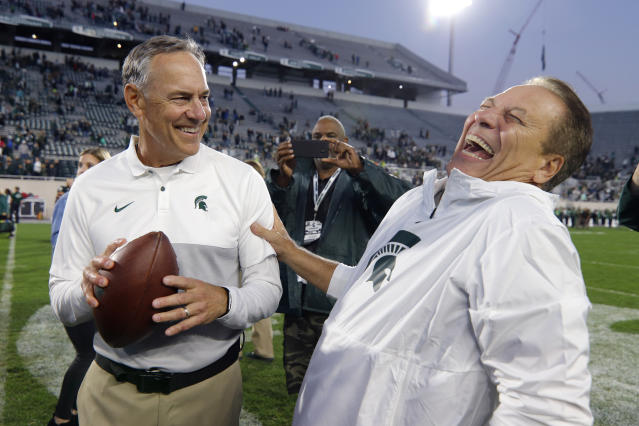 Michigan State football coach Mark Dantonio, left, and basketball coach Tom Izzo react after Dantonio was given a game ball commemorating him as the winningest football coach in Michigan State history following an NCAA college football game against Indiana, Saturday, Sept. 28, 2019, in East Lansing, Mich. (AP Photo/Al Goldis)
