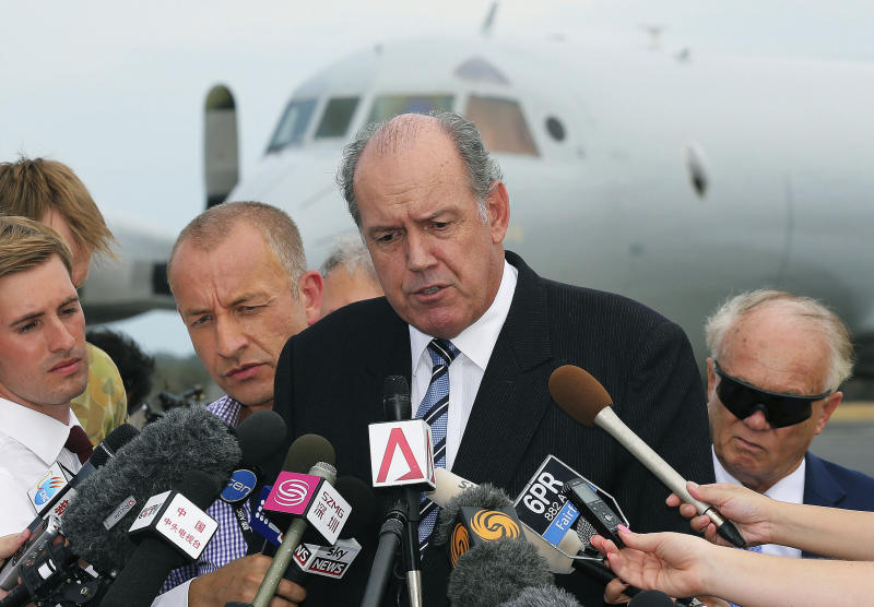 "FILE - In this March 25, 2014 file photo, Australia's Defense Minister David Johnston, center, speaks to the media about developments in the search for the missing Malaysia Airlines Flight 370 in Perth, Australia. Not one object has been recovered from the missing airliner that Malaysian officials are now convinced plunged into the southern Indian Ocean 17 days ago. Australian Defense Minister Johnston said, ""The turning point for us, I think, will be when we pull some piece of debris from the surface of the ocean and positively identify it as being part of the aircraft."" (AP Photo/Rob Griffith, File)"