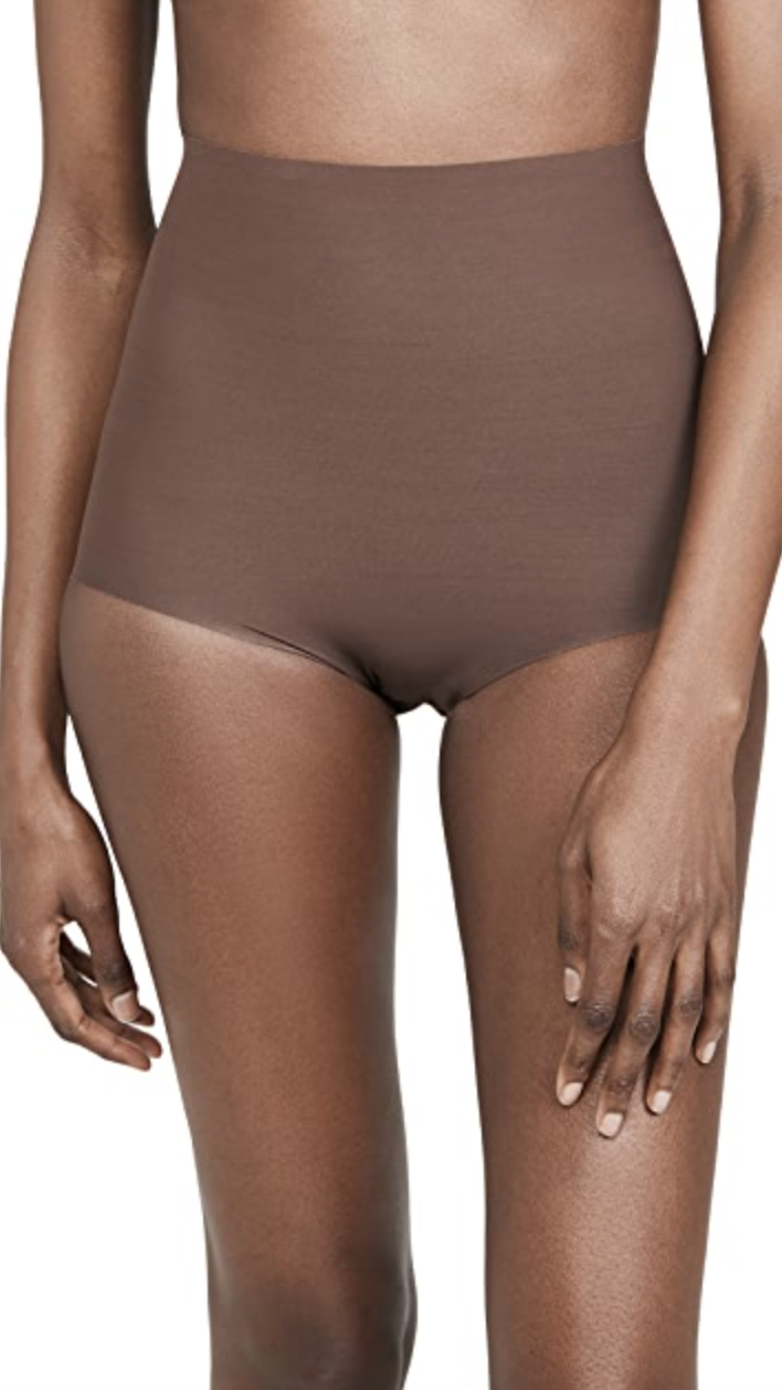 model with upper body cut off wearing brown high waisted control shorts