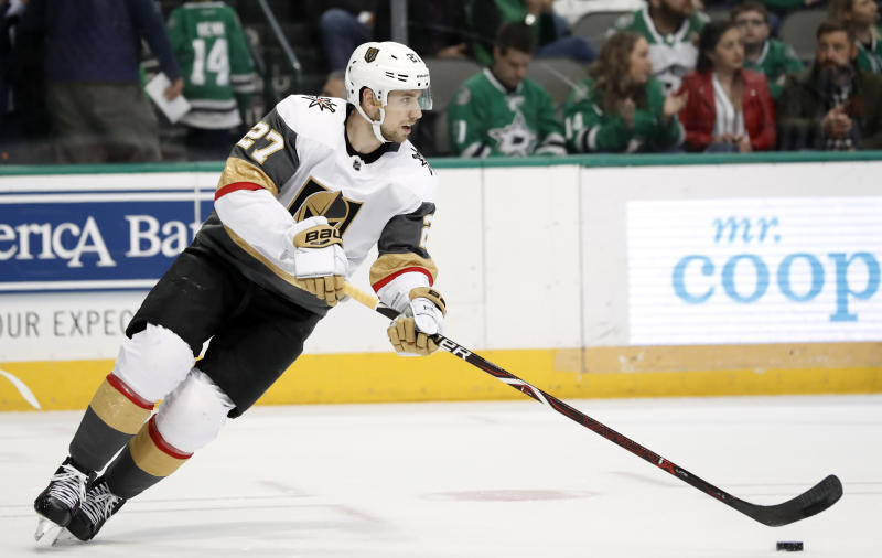 Vegas Golden Knights' Shea Theodore (27) moves the puck against the Dallas Stars during an NHL hockey game in Dallas, Friday, March 15, 2019. (AP Photo/Tony Gutierrez)
