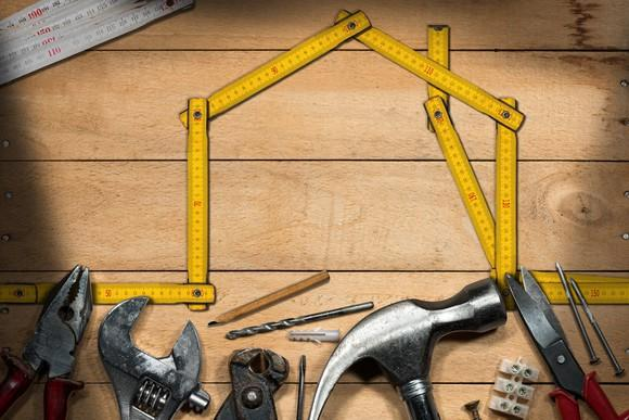 a07d8560d38 Home-improvement tools lined up under a yellow measuring tape shaped like  the outline of