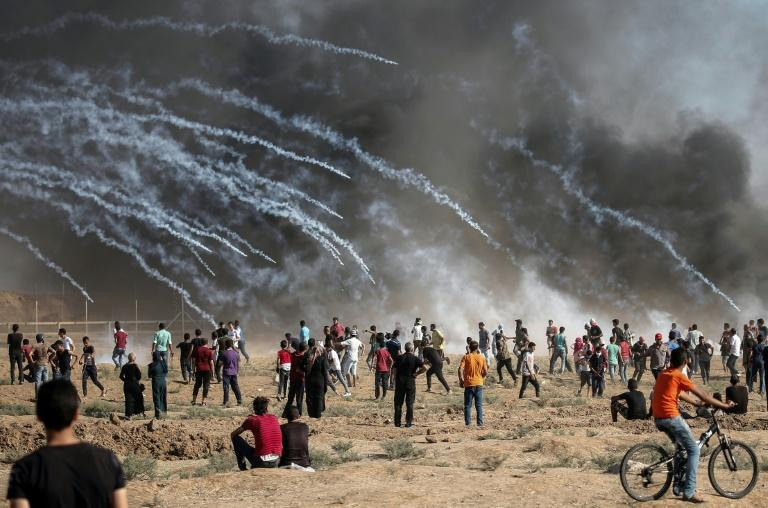 A picture taken on August 17, 2018 shows tear gas canisters fired by Israeli forces raining down on Palestinian protesters during a demonstration along the border of the Gaza Strip