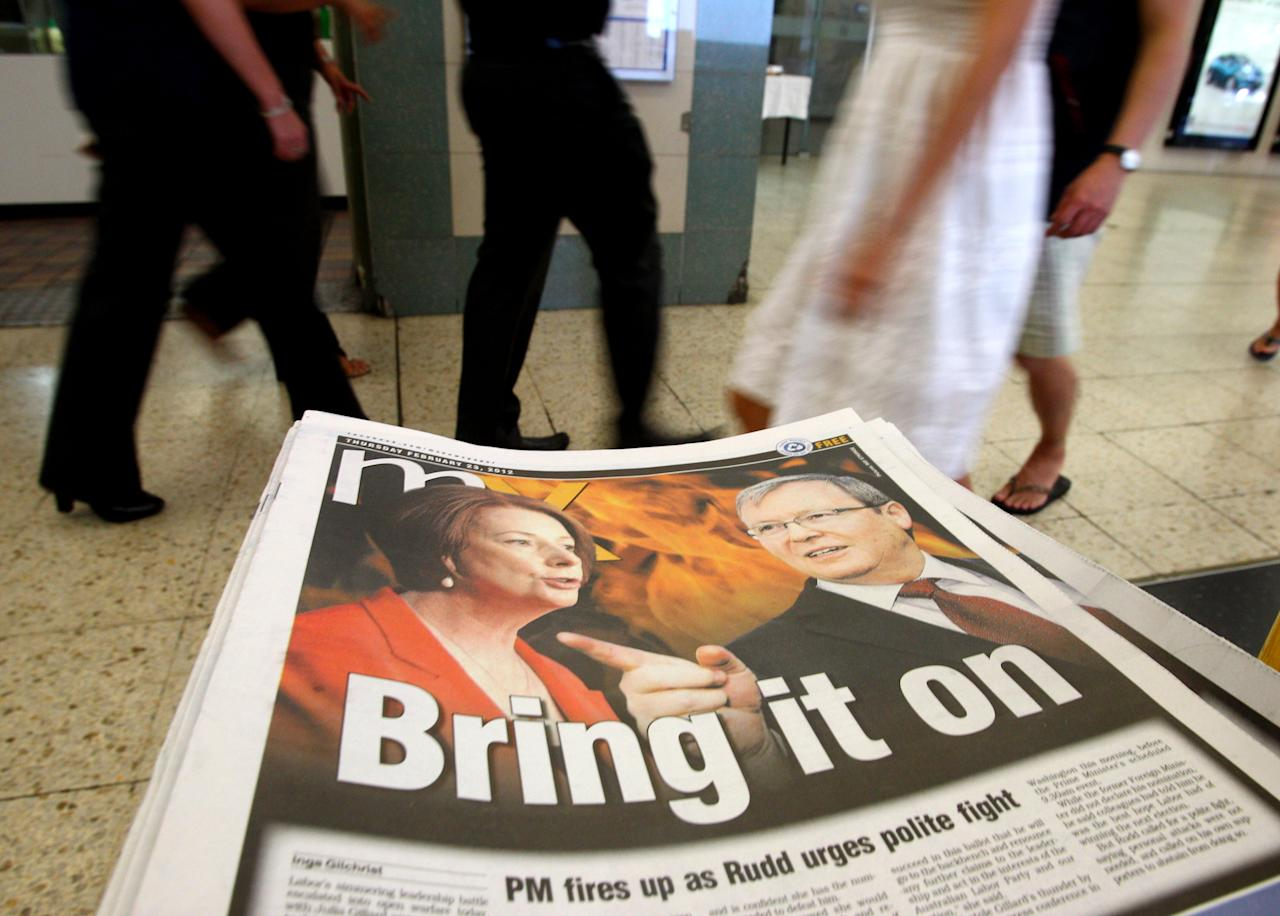 Photos of Australian Prime Minister Julia Gillard, left, and former Foreign Minister Kevin Rudd, are displayed on a newspaper at a train station Thursday, Feb. 23, 2012, in Sydney. Rudd, who resigned as foreign minister Wednesday during an official visit to the U.S., told reporters in Washington that night that he thinks Labor will lose next year's elections if Gillard remains leader, and that government colleagues are encouraging him to run in a a leadership ballot. (AP Photo/Rick Rycroft)
