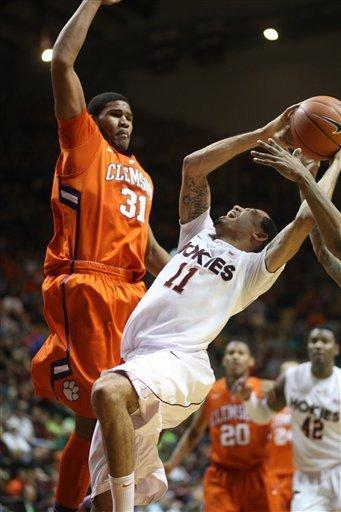 Virginia Tech guard Erick Green (11), right, is knocked down at the basket by Clemson forward Devin Booker (31) during the first half of an NCAA college basketball game in Blacksburg, Va., Saturday, March 2, 2013. (AP Photo/Daniel Lin)