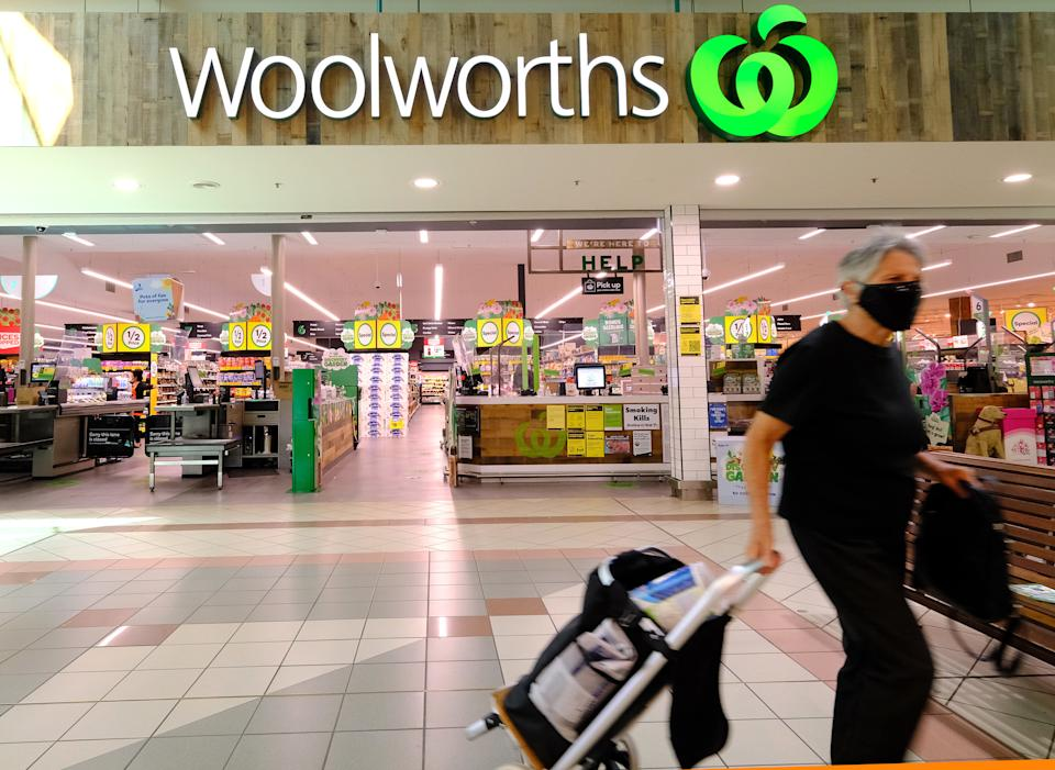 Pictured is a Woolworths store and a man walking out with his groceries.