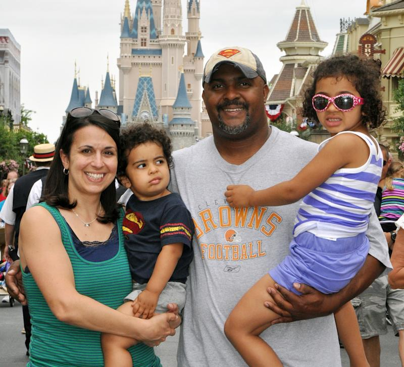 "This June 2013 photo provided by Disney PhotoPass Service shows Creed Anthony of Indianapolis with his daughter Sophie, 5, son Isaac, 2, and wife Amal, on a visit to Disney World's Magic Kingdom in Lake Buena Vista, Fla. Anthony is an example of a new generation of hands-on dads who don't just change the occasional diaper but who view ""parenting as a partnership,"" as he put it,  by being as involved in childrearing as moms. (AP Photo/Disney PhotoPass Service)"