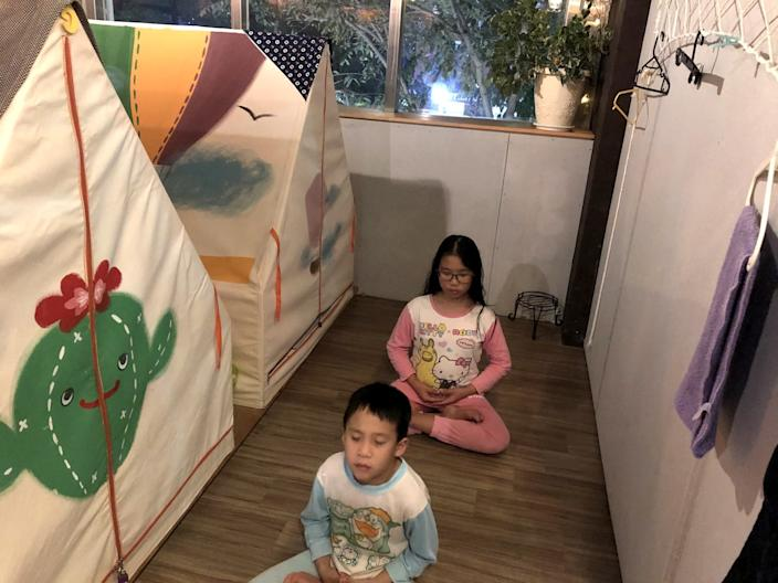 "Yu Chung-chieh, 7, foreground, and Yu Shan-chen, 12, say prayers before bedtime at Ponponwu, an indoor campground in Taiwan. <span class=""copyright"">(Ralph Jennings)</span>"