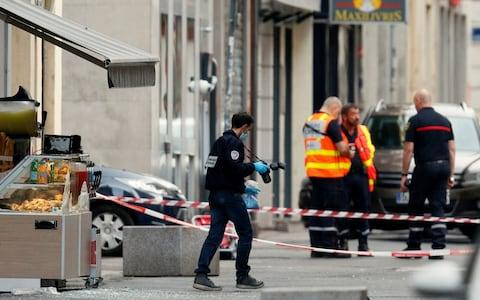 A police officer carrying evidence at the site of a suspected bomb attack in central Lyon - Credit: Emmanuel Foudrot/Reuters