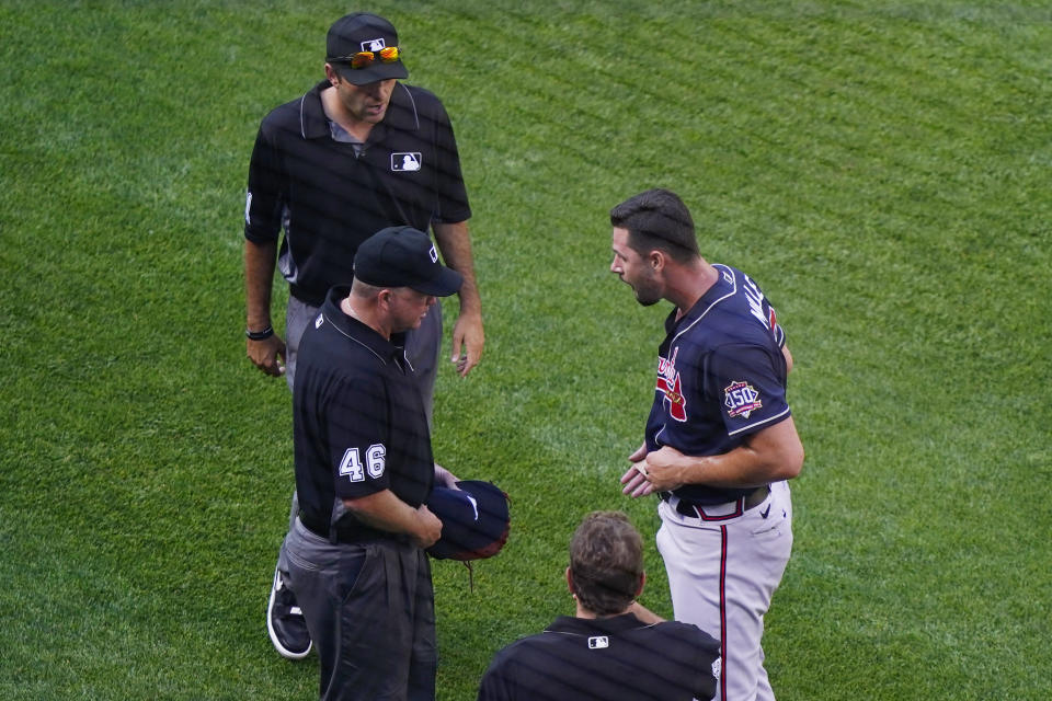 Atlanta Braves starter Kyle Muller, right, reacts as third base umpire Ron Kulpa (46) asks to see what is beneath his belt after he pitched during the first inning of a baseball game against the New York Mets, Monday, June 21, 2021, in New York. (AP Photo/Kathy Willens)